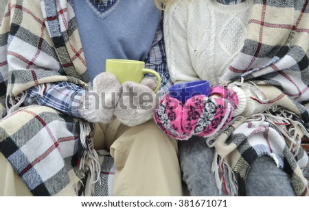young beloved couple warming themselves in the winter park. couple's hands with cups of hot tea.Couple in love. Relations. Love Winter snow park.Couple pours tea in mug from thermos at winter Park.