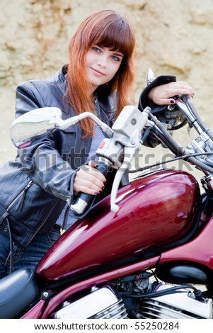 Young biker girl on a motorcycle - stock photo