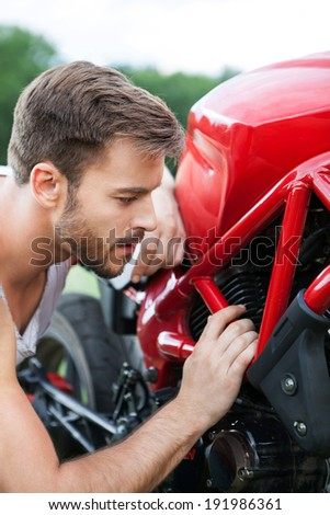 Young biker looks at the motorcycle engine