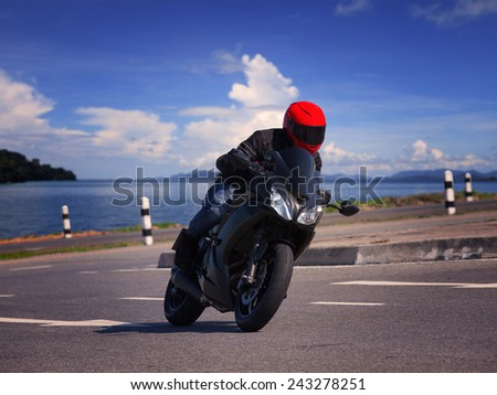 young biker man riding motorcycle on asphalt road against beautiful sea water background - stock photo