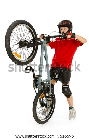 Young biker picking up front wheel his BMX. He' s in helmet and kneepad. Isolated on white background. - stock photo