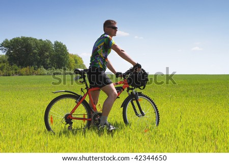 Young Biker tourist relaxation in green field