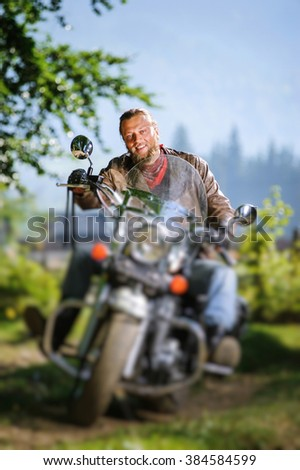 young biker with beard driving his cruiser motorcycle in the forest and smiling. Man is wearing leather jacket and blue jeans. Tilt shift lens blur effect - stock photo
