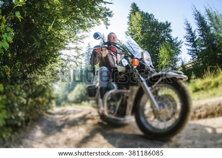 Young biker with beard driving his cruiser motorcycle in the forest. Man is wearing leather jacket and blue jeans. Low point of view. Tilt shift lens blur effect - stock photo