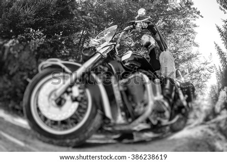 Young biker with beard driving his cruiser motorcycle on road in the forest. Man is wearing leather jacket and  jeans. Low point of view. Tilt shift lens blur effect. Black and white - stock photo