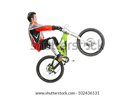 Young biker with his mountain bike jumping isolated on white background - stock photo