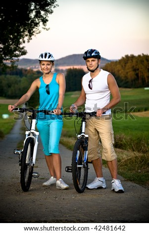 young biking couple on countryside road - stock photo