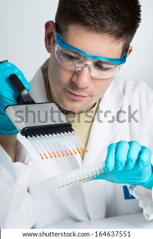 Young biologist sets PCR reaction with multichannel pipette  - stock photo