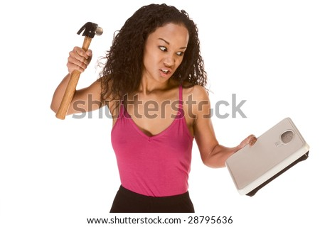 Young biracial dark skinned female of Chinese, African-American, German and Middle Eastern origin in tank top hit weight scales by hammer, blaming it for failure of her dieting and weight-loss effort - stock photo