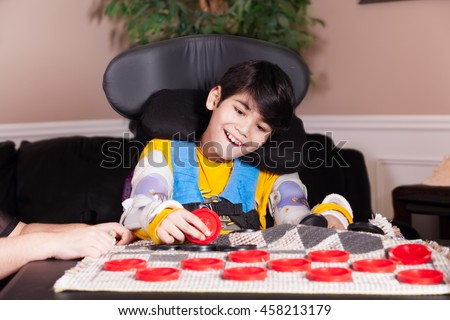 Young biracial disabled boy in wheelchair playing checkers at home. Child has cerebral palsy. - stock photo