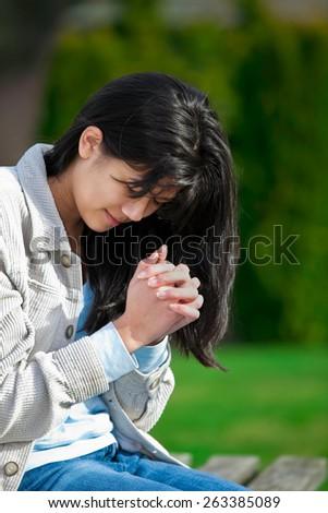 Young biracial teen girl praying outdoors on bench - stock photo