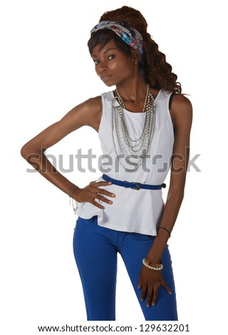 Young black african adult woman in a casual outfit of Blue pants and a white shirt with a hairpiece and jewelry isolated on a white background