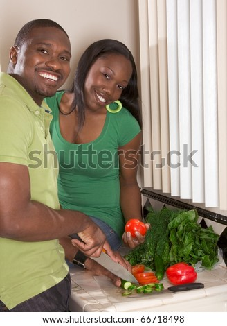 Young black African American couple preparing vegetable salad on kitchen countertop - stock photo