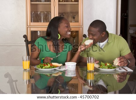 Young black African American couple sitting by glass table and eating meal of salad, bagels with cream cheese and orange juice - stock photo