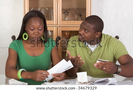 Young black African American couple sitting by glass table and trying to work through pile of bills, frustrated by amount of expenses during economic crises recession times - stock photo