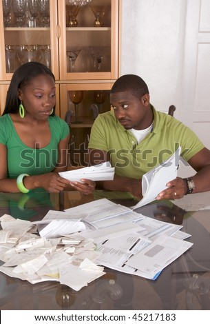 Young black African American couple sitting by glass table and working through pile of bills, frustrated by amount of expenses during economic crises recession times hoping for stimulus plan to work - stock photo
