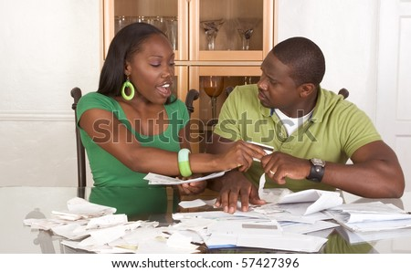 Young black African American couple sitting by table and trying to work through pile of bills, frustrated by amount of expenses during economic crises recession times hoping for stimulus plan to work - stock photo