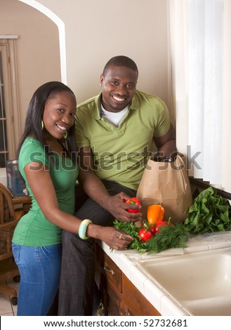 Young black African American couple sorting vegetable on kitchen countertop - stock photo