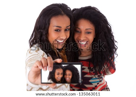 Young black african american teenage girls taking pictures with cell phone, isolated on white background - african people - stock photo