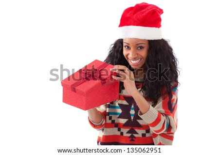 Young black African American woman wearing a santa hat opening a gift box, isolated on white background - stock photo