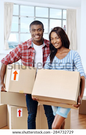 young black african couple moving boxes into new home together making a successful life - stock photo
