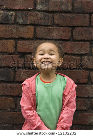 Young black baby girl playing in an alley