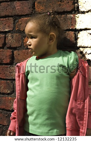 Young black baby girl playing in an alley - stock photo