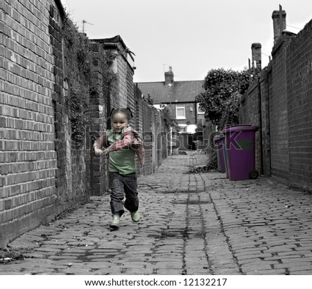 Young black baby girl playing on cobble stoned alley - stock photo