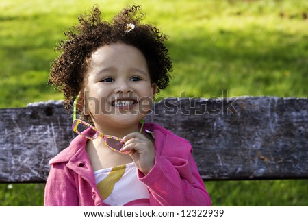Young black baby girl with glasses smiling - stock photo