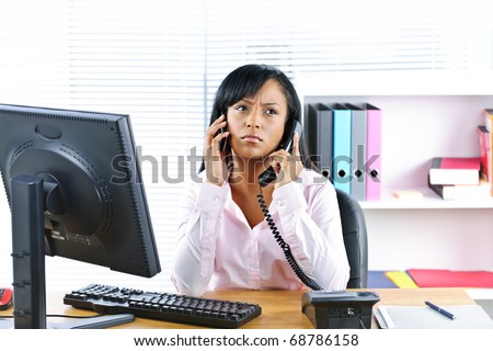 Young black business woman multitasking using two phones in office - stock photo