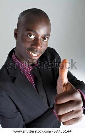 Young black businessman with suit over grey background. He is giving a thumbs up sign. - stock photo