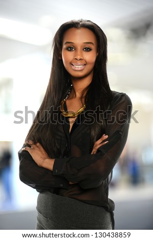 Young black  Businesswoman smiling and with her arms crossed - stock photo