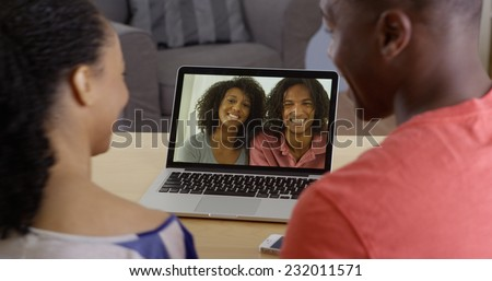 Young black couple having internet video chat with two friends on laptop - stock photo