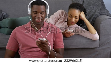 Young black couple listen to music and taking picture with smart phones