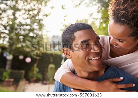 Young black couple piggyback in garden looking at each other