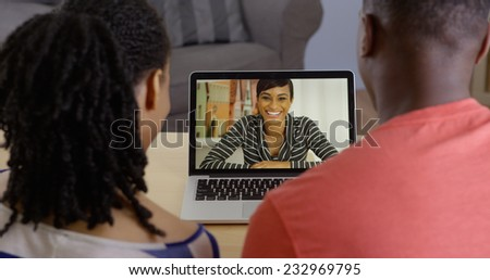 Young black couple talking to friend over laptop video chat - stock photo