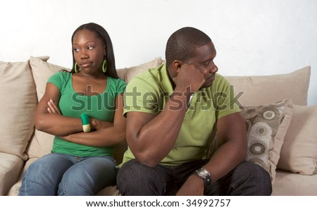 Young black ethnic African-American couple at odds and bad mood not talking with each other and looking away after heated argument - stock photo
