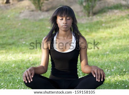 Young black girl doing yoga in the park - stock photo