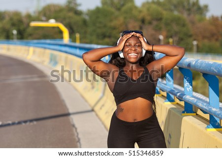 Young black girl with earphone on the street