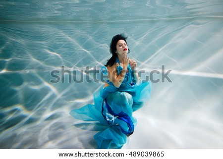 Young black-haired woman in blue dress poses with her eyes close underwater.