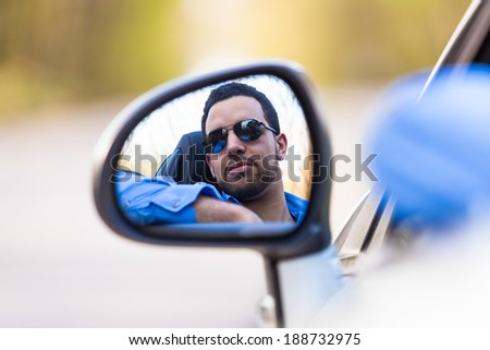 Young black latin american driver  driving his new car - stock photo