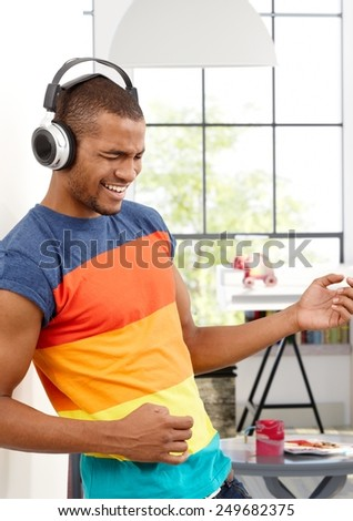 Young black man enjoying music through headphones eyes closed, pretending to play a guitar. - stock photo