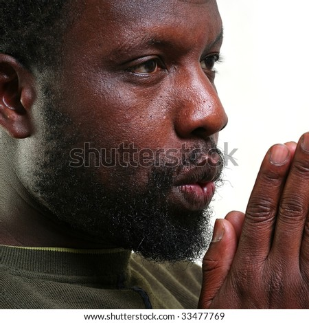 Young black man holds before itself the palms of hands combined together and blows on them, isolated on a white background, please see some of my other parts of a body images   - stock photo