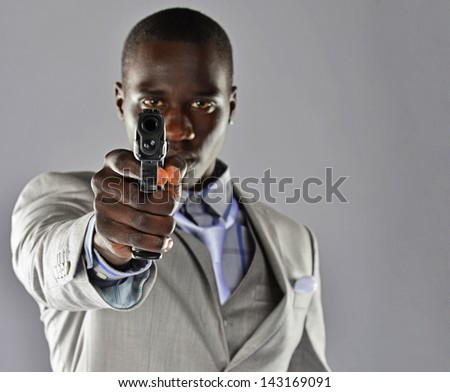Young black man in a suit aiming a handgun directly at the camera. - stock photo