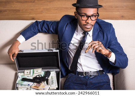 Young black man is wearing suit and hat with gun and money. - stock photo