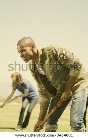 young black man playing field hockey - stock photo
