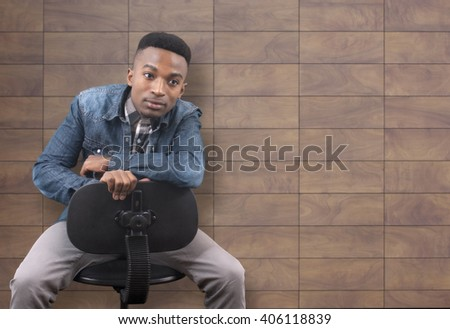 young black man sitting on a desk chair in front of a tile wall - stock photo