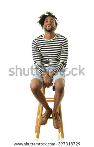 Young black man smiling seating isolated on a white background - stock photo