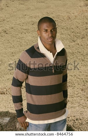 young black man standing in the grass - stock photo