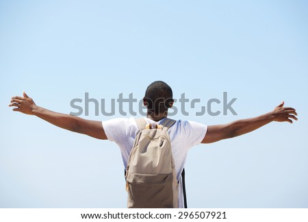 Young black man standing with arms outstretched from behind - stock photo